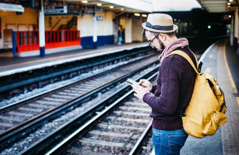 man in brown hoodie standing in front of train railway
